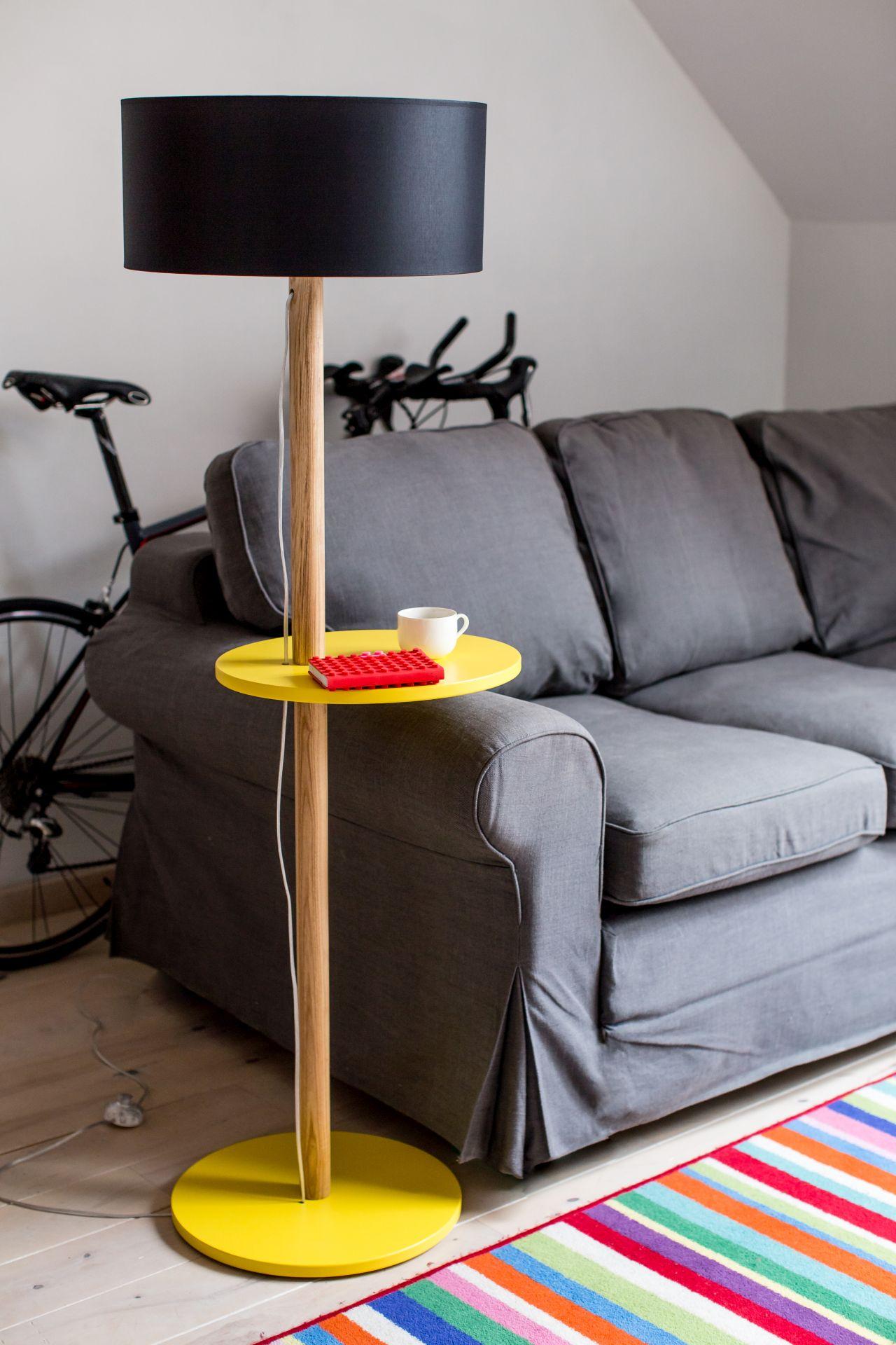 Żółta drewniana lampa stojąca z podstawka przy kanapie